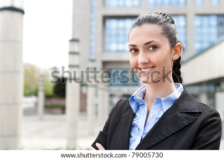 businesswoman outside a modern office building, smiling and looking at camera