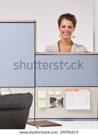 Businesswoman peering over cubicle wall - stock photo