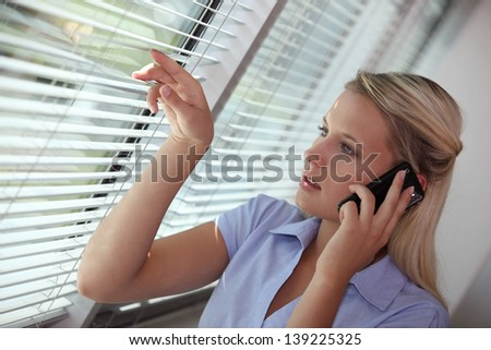 Businesswoman peering through blinds during call - stock photo