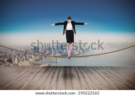 Businesswoman performing a balancing act against city projection on wall
