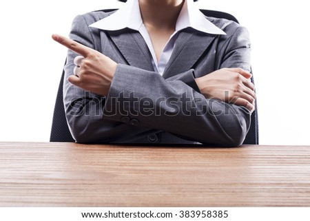 Businesswoman pointing and showing something at desk.