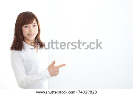 Businesswoman pointing at a blank board - stock photo