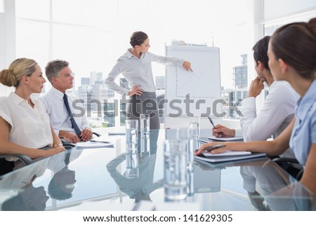 Businesswoman pointing at a chart on a whiteboard during a meeting - stock photo