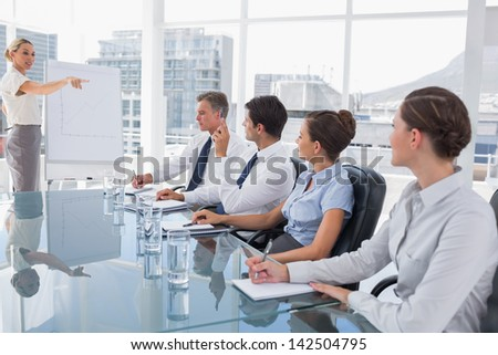 Businesswoman pointing at a colleague who is asking something during a meeting - stock photo