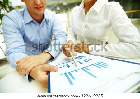 Businesswoman pointing at chart in document held by her colleague - stock photo