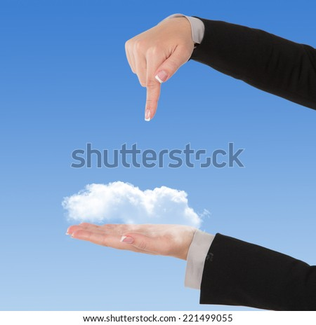 Businesswoman pointing at cloud, computing concept