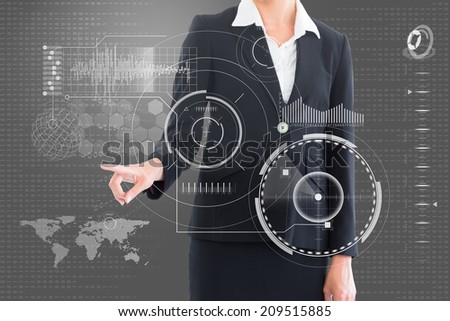Businesswoman pointing at interface somewhere against grey vignette - stock photo