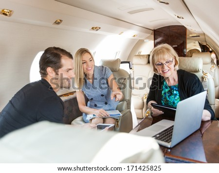 Businesswoman pointing at laptop to colleagues while discussing in private jet - stock photo