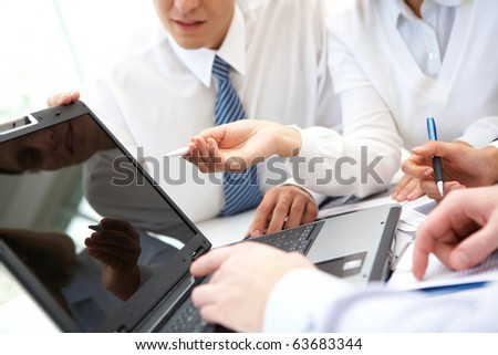Businesswoman pointing at lcd screen while explaining something at meeting - stock photo