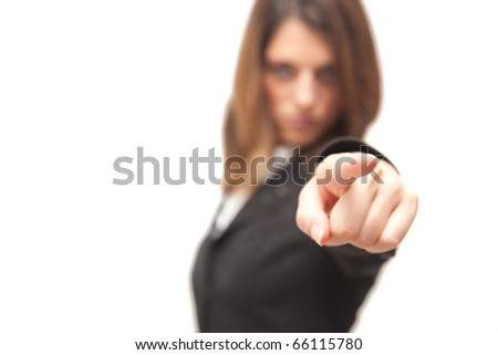 Businesswoman pointing at the camera, focus on the thumb and blurred background - stock photo