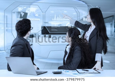 Businesswoman pointing at virtual screen while explaining financial graph and business solution on her partners - stock photo