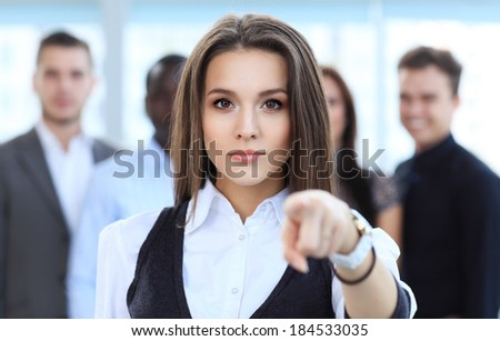 Businesswoman pointing her finger at you on the background of business people  - stock photo