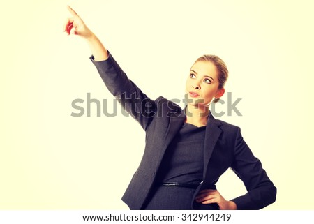 Businesswoman pointing high on copyspace. - stock photo