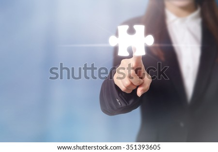 Businesswoman pointing jigsaw puzzle piece. Concept for business success. - stock photo