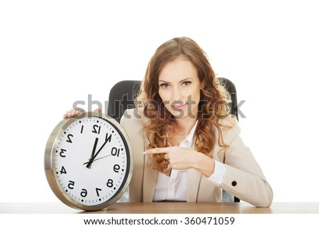 Businesswoman pointing on a clock by a desk.