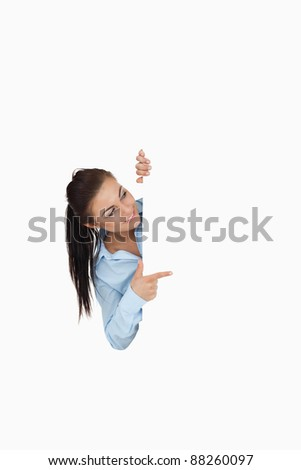 Businesswoman pointing while looking around the corner against a white background - stock photo