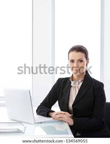 Businesswoman portrait in office, sitting at desk with laptop computer, smiling at camera, copyspace. - stock photo