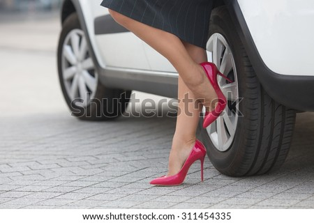 Businesswoman posing near white car and showing her slim and slender legs near her car. Successful lady in grey skirt posing on pink high heels. - stock photo