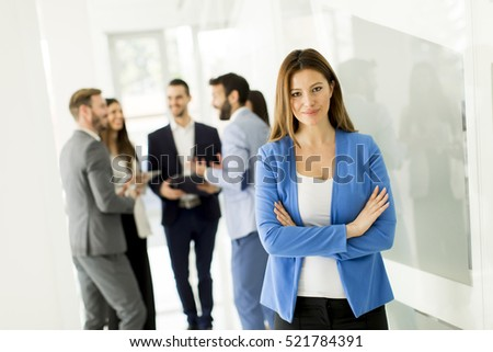 Businesswoman posing while others business people talking in background