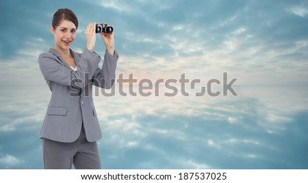 Businesswoman posing with binoculars against clouds reflected on water