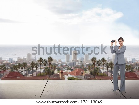 Businesswoman posing with binoculars against large city on the horizon