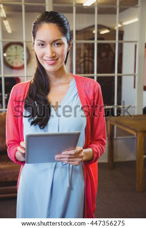 Businesswoman posing with her tablet at work