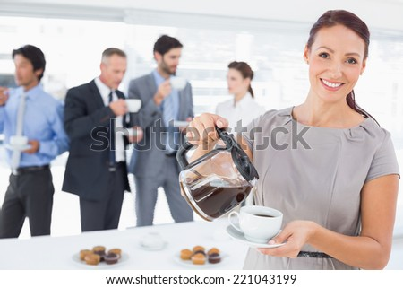 Businesswoman pouring herself some coffee at the office - stock photo