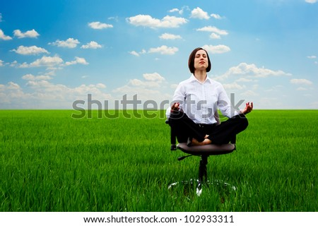 businesswoman practicing yoga at the meadow at sunny day