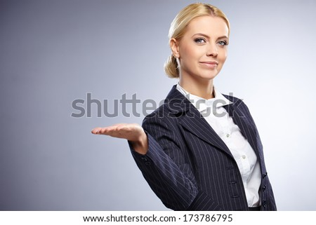 businesswoman presenting something on grey background - stock photo