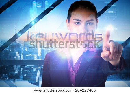 Businesswoman presenting the word keywords against room with large window looking on city - stock photo