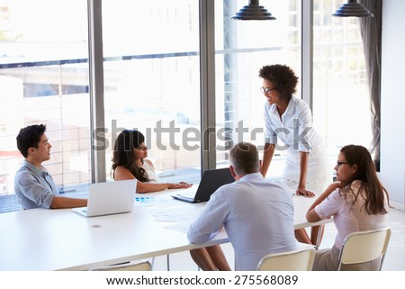 Businesswoman presenting to colleagues at a meeting - stock photo