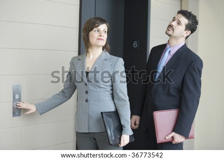 Businesswoman pressing button for elevator in an office building with a businessman standing beside her - stock photo