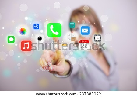 Businesswoman pressing colorful mobile app icons with bokeh background  - stock photo