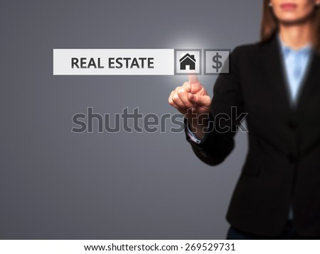 Businesswoman pressing real estate button on virtual screens.Women finger on home icon. Isolated on grey. Business, technology, internet and networking concept - Stock Image