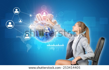 Businesswoman pressing touch screen button on virtual interface featuring Globe with buildings on top and network with person icons, on blue background. Element of this image furnished by NASA - stock photo