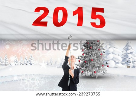 Businesswoman pulling a chain against christmas tree in snowy landscape - stock photo