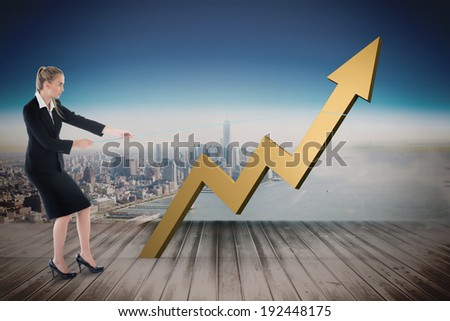 Businesswoman pulling a rope around arrow against city projection on wall
