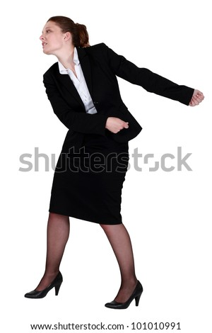 Businesswoman pulling an invisible chain - stock photo