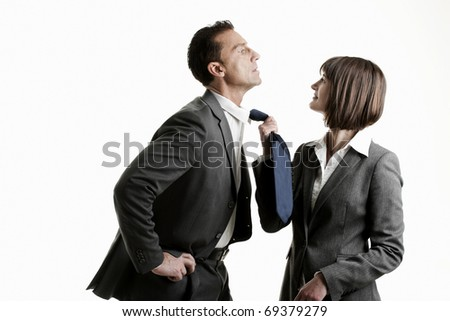 Businesswoman pulling her colleague from his tie - stock photo
