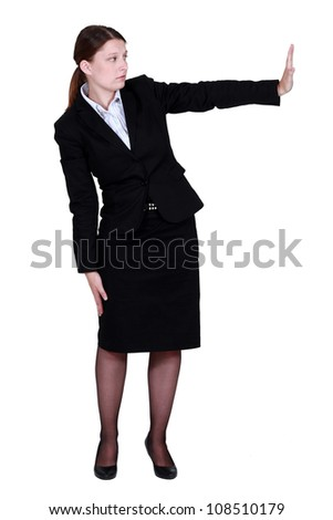 Businesswoman pushing an invisible wall - stock photo