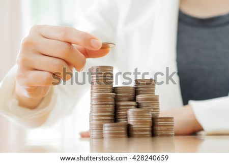 Businesswoman put coins to stack of coins