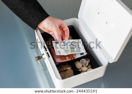 Businesswoman put five euro into safe box closeup - stock photo