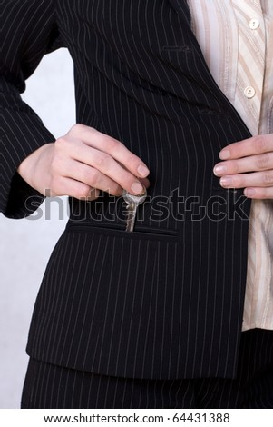 Businesswoman putting a key to the pocket - stock photo