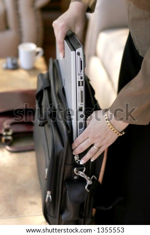 Businesswoman putting away or pulling out a laptop computer from its travel case (shallow focus point on side of laptop and her hand). - stock photo