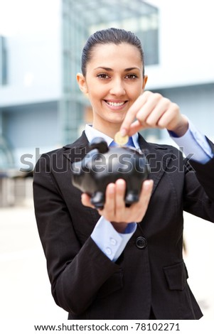 businesswoman putting coins money in piggy bank in front her office building - stock photo