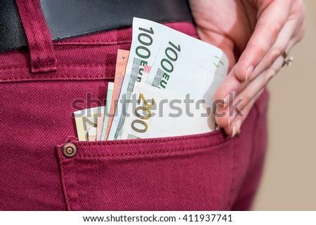 Businesswoman  putting euro money banknotes in pocket - stock photo