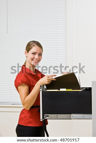 Businesswoman putting file in file cabinet - stock photo
