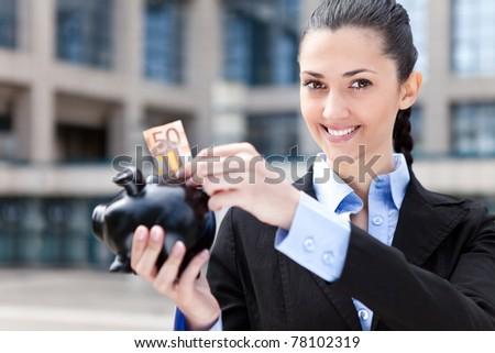 businesswoman putting money in piggy bank, outdoor - stock photo