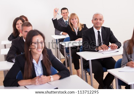 Businesswoman Raising Her Hand In Meeting To Ask Question - stock photo