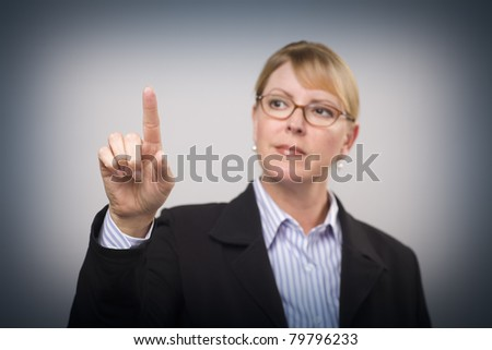 Businesswoman Reaching Out with Finger - Ready for Your Own Buttons or Touch Screen - Focus is On Her Finger. - stock photo